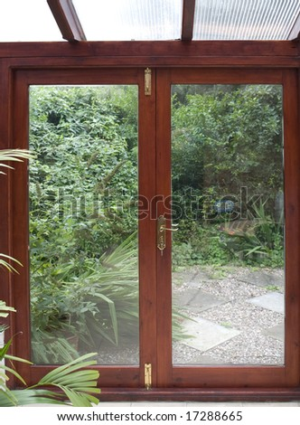 conservatory with door to garden and plants, a room in house next to garden - stock photo