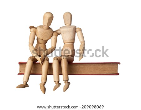 Consolation of a friend depicted by two figurines on a book isolated on white background  - stock photo