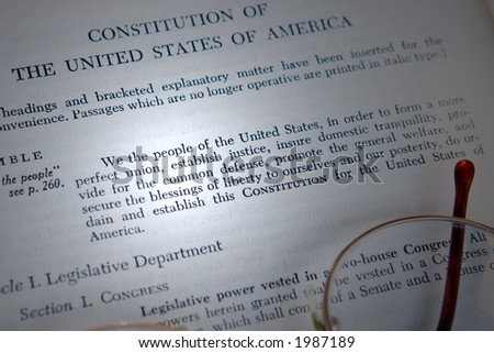 Constitution of the United States being studied, with eye glasses and a beam of light highlighting the text.