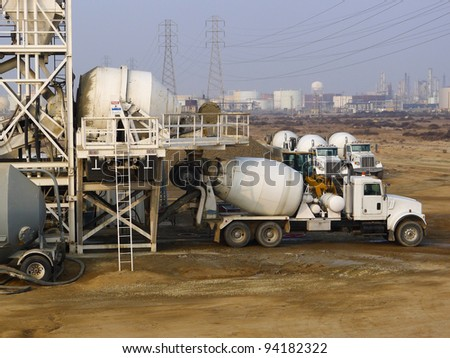 Construction: A transit mix truck for delivering concrete to job site gets loaded at a portable batch plant - stock photo