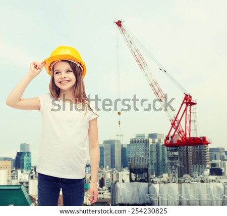 construction and people concept - smiling little girl in protective helmet looking up - stock photo