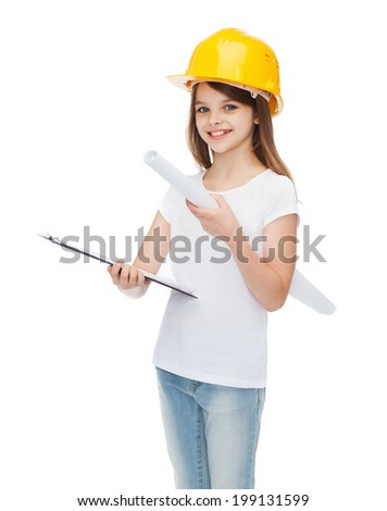 construction and people concept - smiling little girl in protective helmet with clipboard and blueprint - stock photo