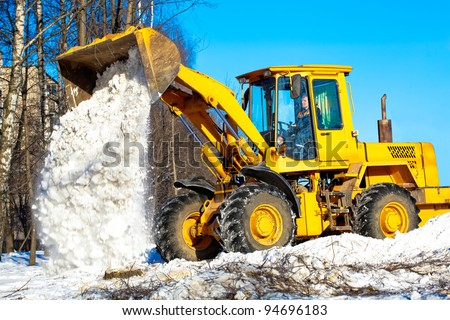Construction and snow removal equipment at work - wheel loader  unloading snow during roadworks