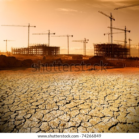 Construction and urban planning concept .Landscape with construction cranes and cracked soil. - stock photo
