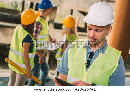 Construction architects using digital tablet in building damaged in the disaster. His colleagues review plan. - stock photo