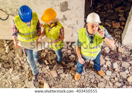 Construction architects using phone in building damaged in the disaster. His colleagues review plan. - stock photo