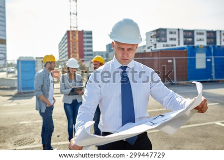 construction, architecture, business, teamwork and people concept - male architect with blueprint over group of builders on construction site - stock photo