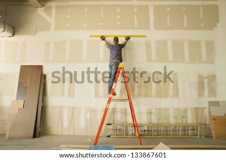 Construction area with man working on ladder - stock photo
