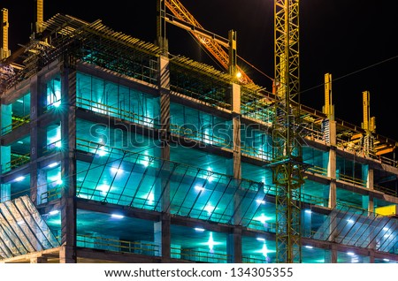 Construction at night with lights against the dark sky - stock photo