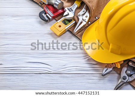 Construction belt hard hat on wooden board maintenance concept.