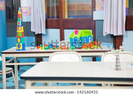 Construction blocks and house on desk in classroom - stock photo