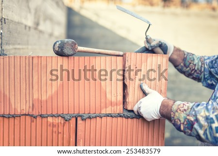 Construction bricklayer worker building walls with  bricks and mortar - stock photo