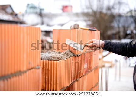 Construction bricklayer worker building walls with fresh bricks and tools - stock photo