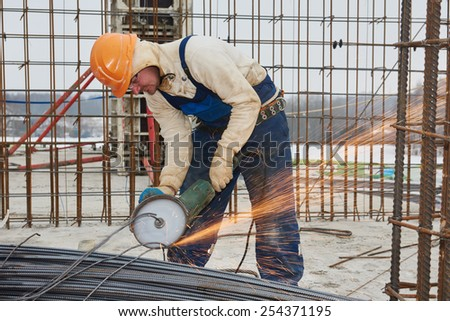 Construction builder worker with grinder machine cutting metal reinforcement rebar rods at building site - stock photo
