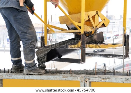 construction building worker at construction site pouring concrete in a form - stock photo
