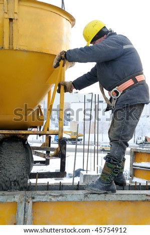 construction building worker at construction site pouring concrete in mould