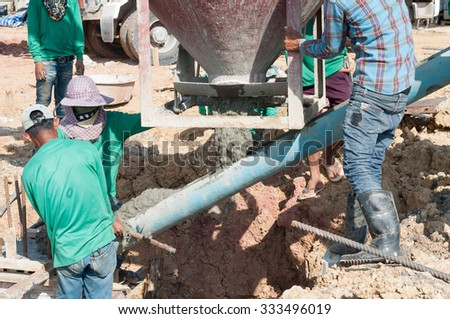 construction building workers at construction site pouring concrete - stock photo