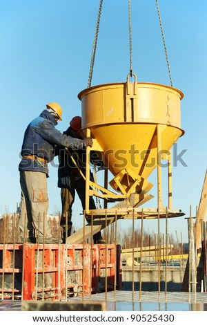 construction building workers at construction site pouring concrete in form - stock photo