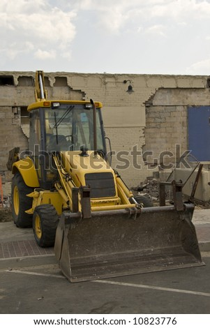 Construction Bulldozer sitting alone near a wall