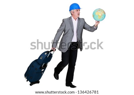 construction businessman holding a globe and a suitcase - stock photo