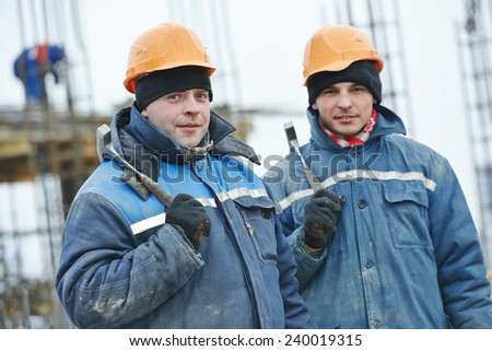 construction carpenter workers at construction site assembling falsework for concrete pouring - stock photo
