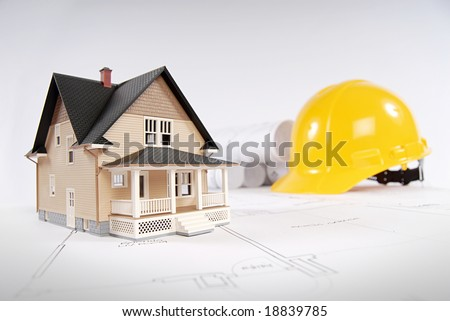 Construction concept with home, blueprints and hardhat - stock photo