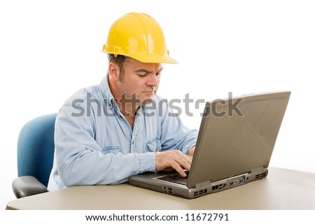 Construction contractor in the office on his laptop.  Isolated on white. - stock photo