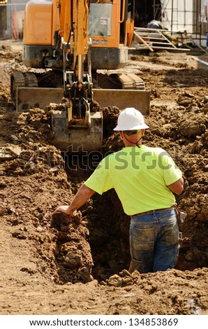 Construction contractor using a small track hoe excavator to dig a water line trench on a new commercial residential development - stock photo