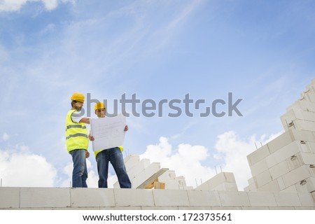 Construction Contractors building a big new home - stock photo