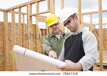 Construction Contractors building a new home - stock photo