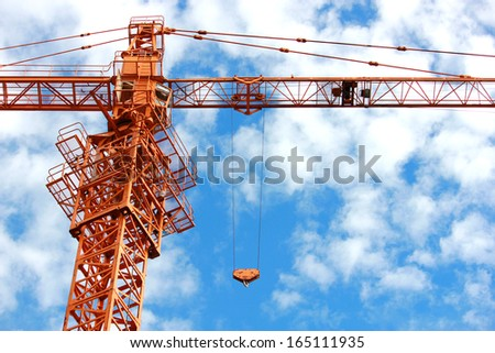 Construction crane against the blue sky,Construction crane on a background of beautiful blue sky with clouds  - stock photo