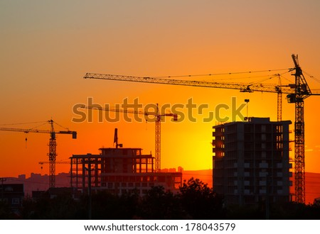 Construction crane and skyscraper at sunset  - stock photo