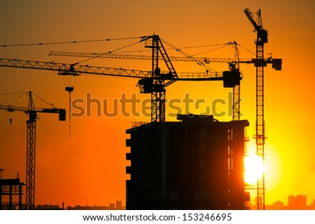 Construction crane and skyscraper in the sunset