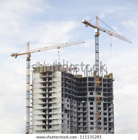 Construction crane at the construction site, on a cloudless sky - stock photo