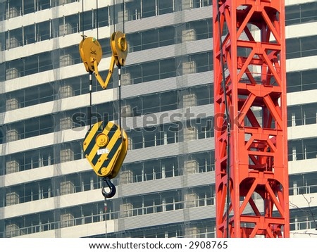 construction crane background with steel hook over construction site background - stock photo