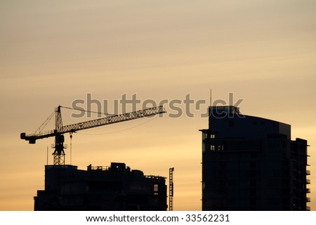 Construction crane building a high rise at dusk - stock photo