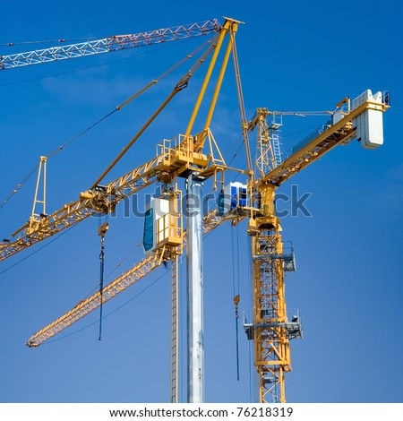 Construction crane isolated on clear blue sky - stock photo