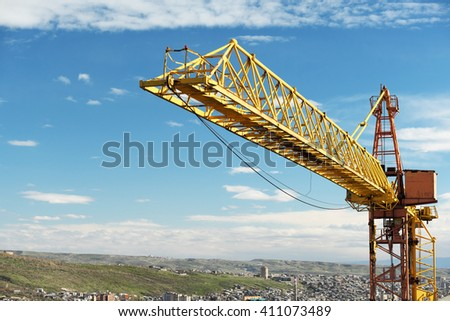 Construction crane tower against a blue sky - stock photo