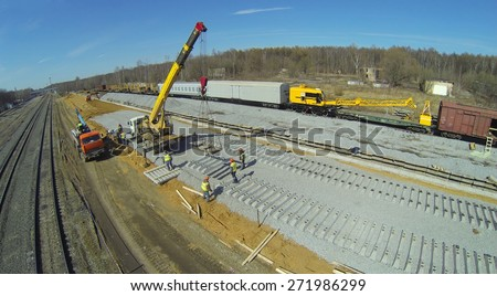 Construction crane with sleepers and workers at construction of new railway lines, aerial view - stock photo