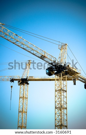 Construction cranes against blue sky - stock photo