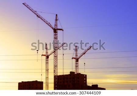 Construction cranes and new buildings silhouette against the backdrop of the sunset sky