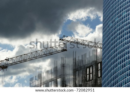 Construction cranes on the construction of office building - stock photo