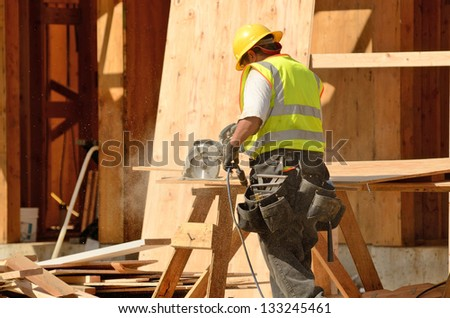 Construction crew using a electric saw on the roof sheeting of a new, two story, commercial apartment building in Oregon - stock photo