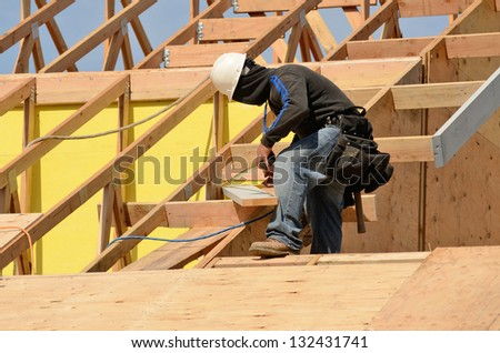 Construction crew working on the roof sheeting and fascia of a new, two story, commercial apartment building in Oregon - stock photo