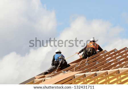 Construction crew working on the roof sheeting and outriggers or ladder of a new, two story, commercial apartment building in Oregon - stock photo