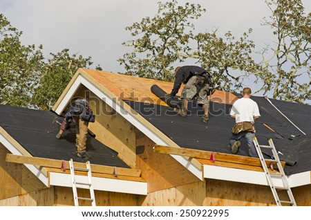 Construction crew working on the roof sheeting of a new, luxury residential home project in Oregon - stock photo