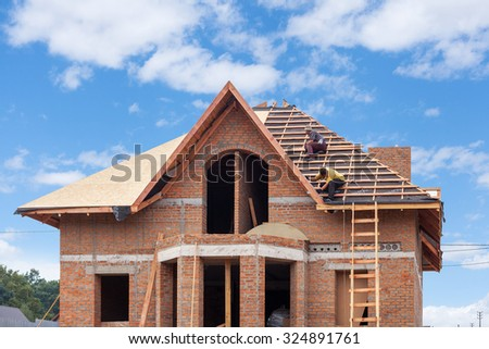 Construction crew working on the roof sheeting of new house made with bricks - stock photo