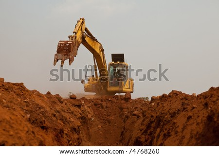 Construction digger excavating pipeline trench - stock photo