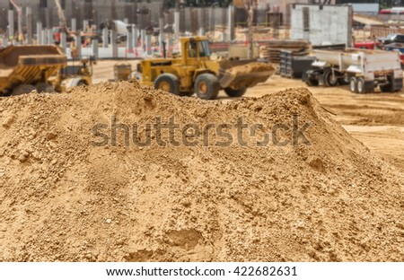 Construction dirt pile at new development worksite. Mound of sandy soil, rocks, and pebbles. Blurred loader vehicle, new building foundation and concrete pylons in background.  - stock photo