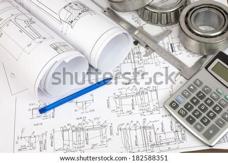 Construction drawings, caliper, bearing, calculator and pen. Desk Engineer - stock photo
